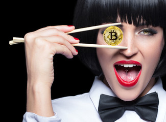 Young woman in bow tie holding bitcoin in front of eye
