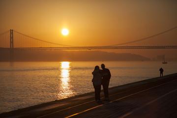 Silhouette eines Paares bei Sonnenuntergang am Fluss mit Brücke