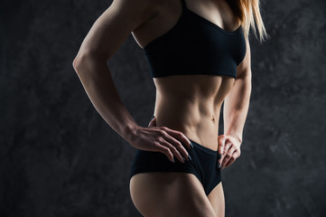 Sports sexy girl with big muscle belly in a black sportswear on a black background. A six-pack on his stomach in black color. Taut, pumped up, firm abdomen