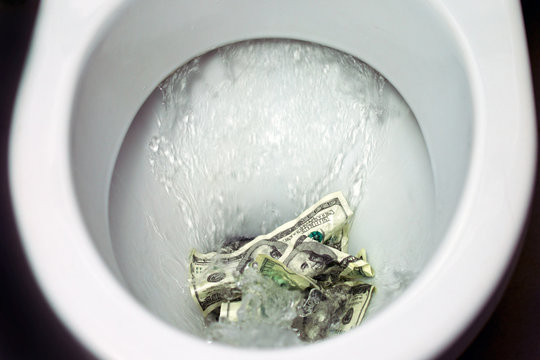 Flush money down the toilet, throws dollar bills in the toilet, loss concept, close up, selective focus