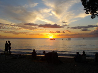 Sunset in Barbados with silhouette of people enjoying drinks on the beach