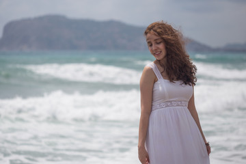 Young brunette female with wavy hair wearing white dress by the