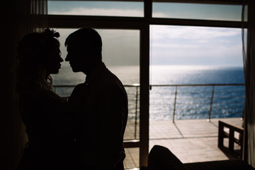 bride and groom silhouette against the sea