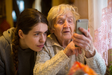 Elderly woman looks at a smartphone, with his adult granddaughter, at home.