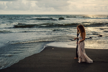 Wedding lovestory, just married couple near the ocean at sunset