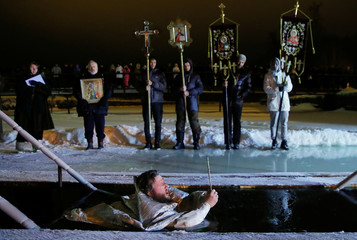 A priest takes a dip into the water during Orthodox Epiphany celebrations in the village of Drachevo, outside Moscow, Russia