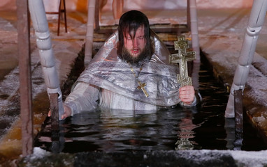 A priest exits the water during Orthodox Epiphany celebrations in the village of Drachevo, outside Moscow, Russia