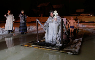 A priest exits the water during Orthodox Epiphany celebrations in the village of Drachevo outside Moscow, Russia