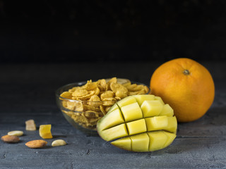 Peeled mango, orange, flakes, and nuts on a dark wooden table.