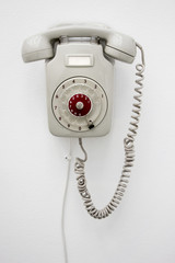 Old fashioned gray rotary telephone hanging on white wall. Vertical photo.