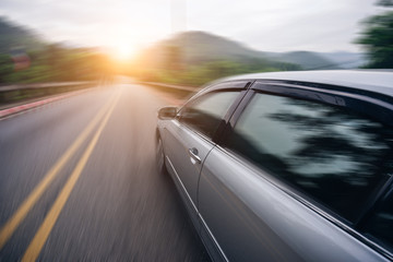 Car driving on asphalt road at sunset go to travel, motion blur
