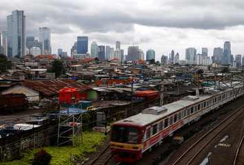 A commuter train is seen against the backdrop of high-rise buildings at Tanah Abang district in Jakarta, Indonesia
