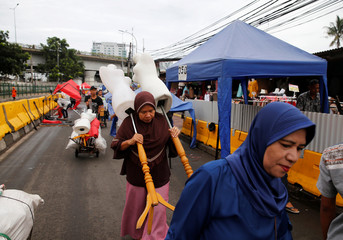 Street vendors carry mannequins as they prepare their stalls aling Tanah Abang street in Jakarta, Indonesia