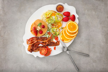 Delicious pancakes with fried bacon, vegetables and fruits on plate