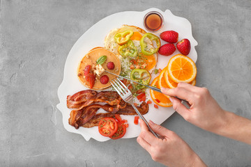 Young woman eating delicious pancakes with fried bacon, vegetables and fruits on plate