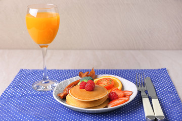 Delicious pancakes with bacon and glass of orange juice served for breakfast on table