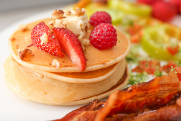 Delicious pancakes with fried bacon on plate, closeup