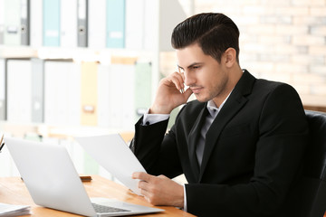 Young man working with laptop and documents in archive