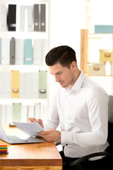 Young man working with laptop and documents in office