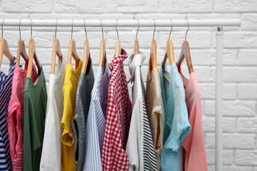 Rack with different clothes near brick wall