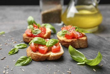 Tasty bruschettas with tomatoes on table