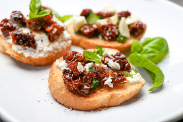 Tasty bruschetta with sun-dried tomatoes on plate, closeup