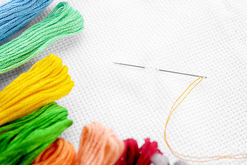 White fabric with colorful threads and sewing needle, closeup