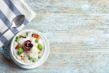 Dish with tasty seafood risotto on wooden background
