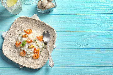 Plate with tasty seafood risotto on wooden background