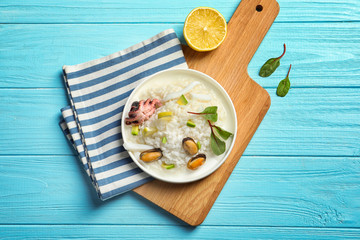 Plate with tasty seafood risotto on wooden table