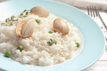 Plate with tasty seafood risotto on table, closeup