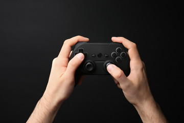 Man holding video game controller on black background