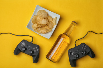Composition with video game controllers, beer and snack on color background