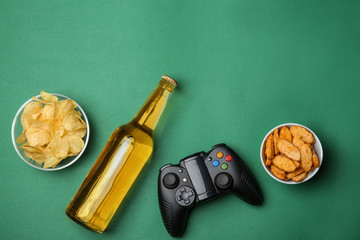 Composition with video game controller, beer and snack on color background