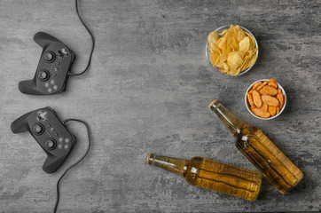 Composition with video game controllers, beer and snack on grey background
