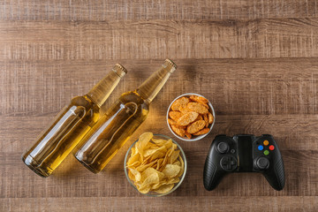 Composition with video game controller, beer and snack on wooden background