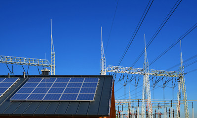 Solar energy panel on the roof of the house in the background  high voltage power substation.