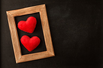 Two red hearts in wooden  picture frame