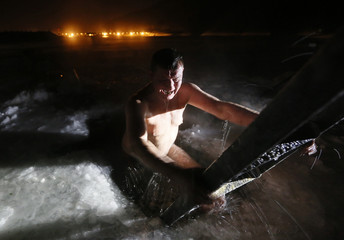 A man reacts after taking a dip in the icy waters of the Yenisei River during Orthodox Epiphany celebrations outside Krasnoyarsk