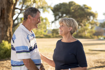portrait of American senior beautiful and happy mature couple around 70 years old showing love and affection smiling together in the park