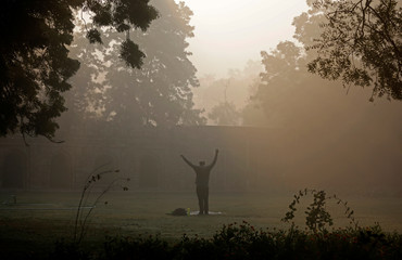 A man exercises at a public park on a foggy winter morning in New Delhi
