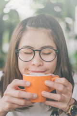 Portrait of asian women feels happy with a cup of hot coffee drink.