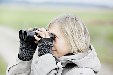 Side view of blonde woman holding binoculars