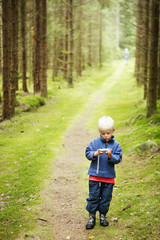 Child standing on path in forest