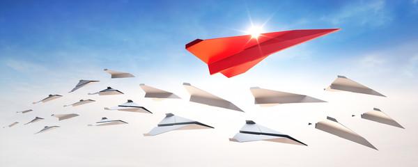 Roter Papierflieger im Sonnenlicht