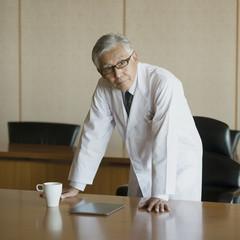 会議室の机に手をつく医者