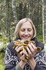 Smiling woman holding freshly picked mushrooms