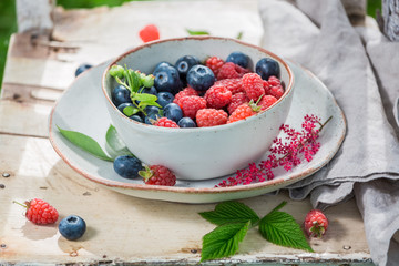 Healthy blueberries and raspberries on old wooden rustic table
