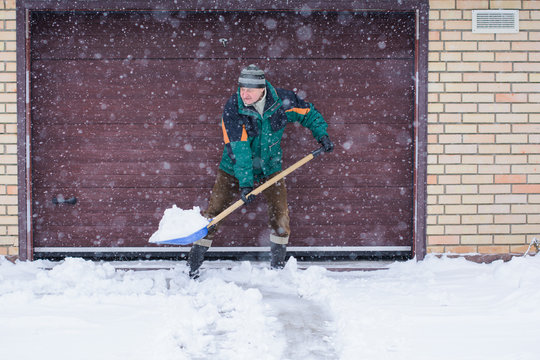 A man cleans snow in winter weather with a shovel near the garage