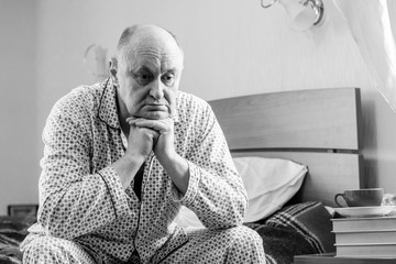 Sick senior man in bed. Problem with a health and bad mood, depression in older people. Unhappy elderly man